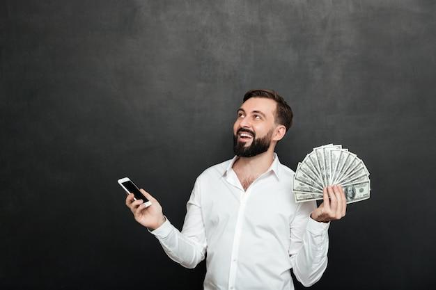Uomo felice in camicia bianca che vince un sacco di soldi in contanti usando il suo telefono cellulare e guardando su grigio scuro