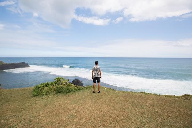 Uomo felice in piedi sulla cima della montagna, guardando oltre l'oceano. successo, vincitore, felicità.