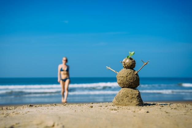 Uomo felice sabbioso e giovane donna sexy sulla spiaggia del mare contro il cielo nuvoloso blu di estate