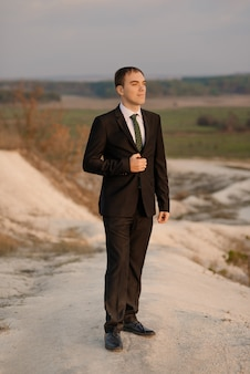 Uomo felice, sposo in cappotto elegante vestito all'aperto su sfondo naturale. sposo alla moda che aspetta la sposa. ritratto emotivo di nozze dello sposo all'aperto al tramonto