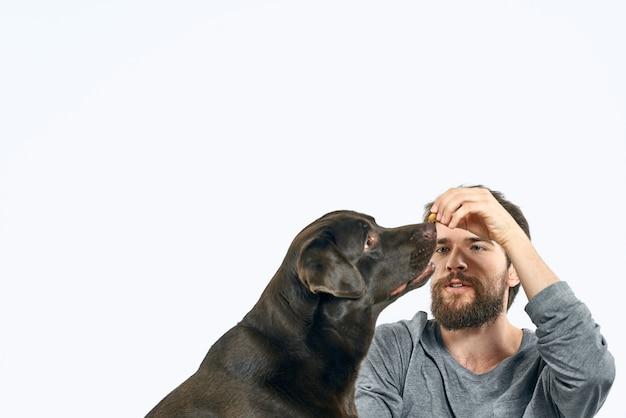 Uomo felice sul divano con il suo cane, isolamento e quarantena con il cane a casa