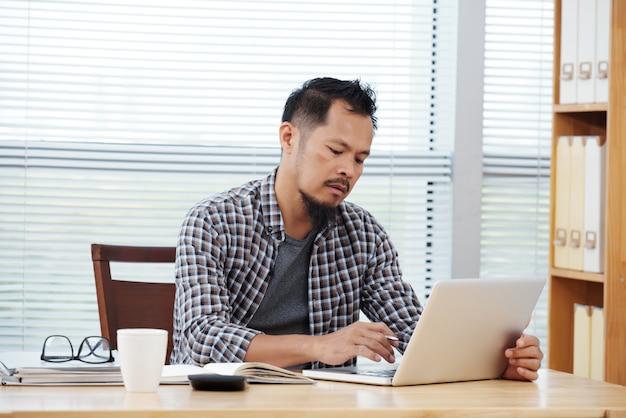 Uomo filippino con indifferenza vestito che si siede nell'ufficio e che lavora al computer portatile