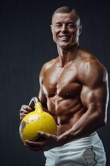 Uomo fitness pompando i muscoli con kettlebell