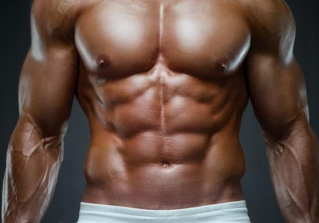 Uomo fitness pompare i muscoli addominali in palestra