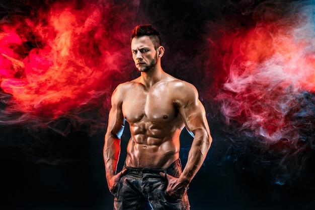 Uomo forte bodybuilder in pantaloni militari con addominali perfetti, spalle, bicipiti, tricipiti, petto