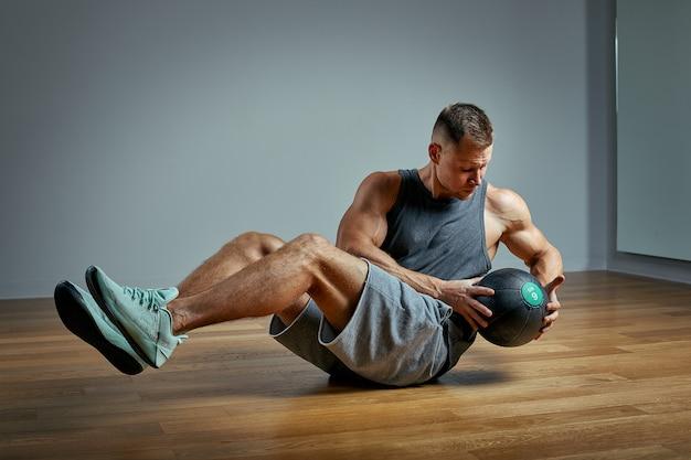 Uomo forte che fa esercizio con la palla medica. foto del fisico perfetto dell'uomo su fondo grigio. forza e motivazione.