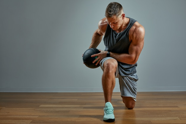 Uomo forte che fa esercizio con la palla medica. foto del fisico perfetto dell'uomo sulla parete grigia. forza e motivazione.
