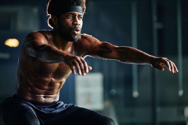 Uomo forte che fa esercizio di squat