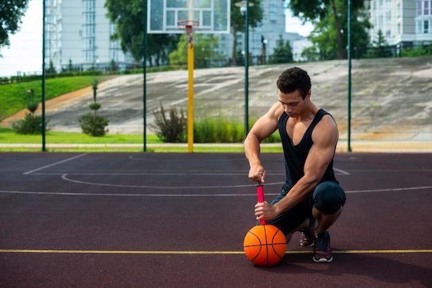 Uomo forte che gonfia una palla a distanza