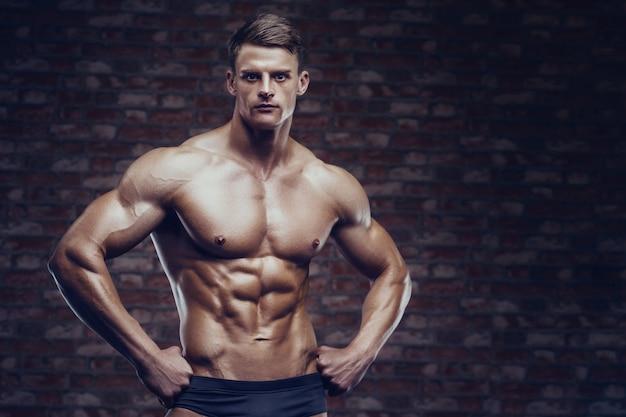 Uomo forte culturista pompare i muscoli addominali