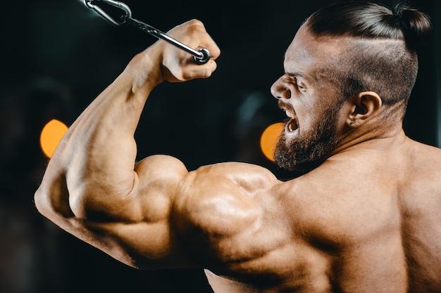 Uomo forte del culturista che pompa i muscoli del bicipite