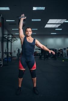 Uomo forte in abiti sportivi che fa esercizio con kettlebell