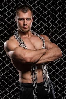 Uomo forte sul recinto con catene