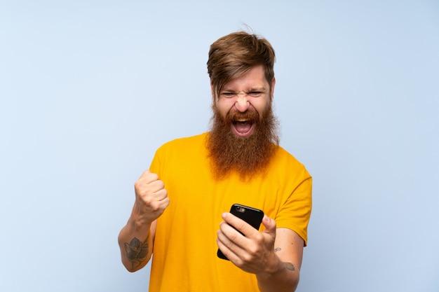Uomo fortunato di redhead con la barba lunga con un cellulare sopra la parete blu isolata