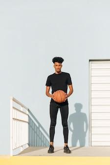 Uomo freddo con pallacanestro sulla strada