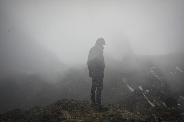 Uomo freddo in piedi sul bordo di una montagna nebbiosa