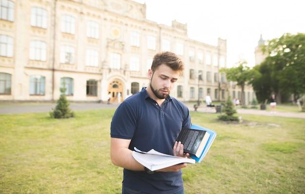 Uomo frustrato con la barba si erge sullo sfondo di un edificio con i libri in mano.