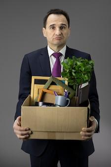 Uomo frustrato con scatola per il trasporto. riduzioni del personale dovute alla crisi finanziaria 2020