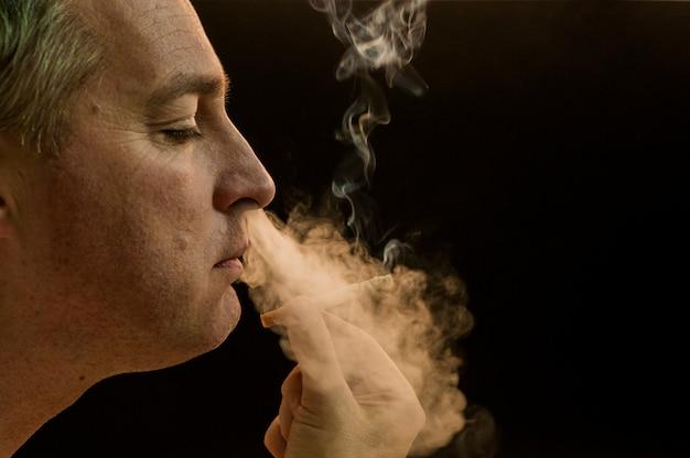 Uomo fumo sigaretta su sfondo nero, giovane uomo fumante sigaretta, uomo mistero con sigaro e fumo isolato su sfondo nero
