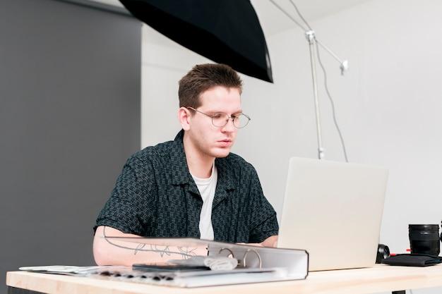 Uomo funzionante del fotografo che si siede e che esamina il suo computer portatile