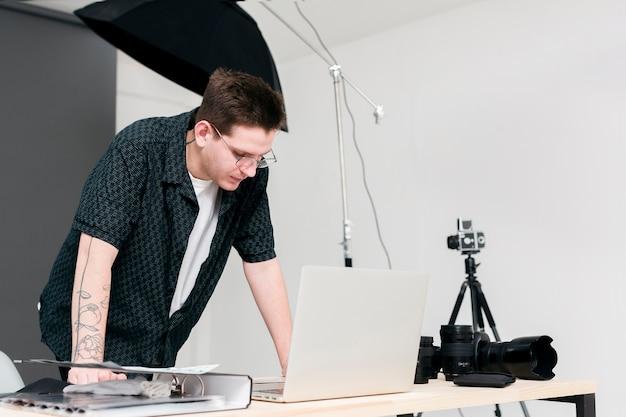 Uomo funzionante del fotografo che sta e che esamina computer portatile