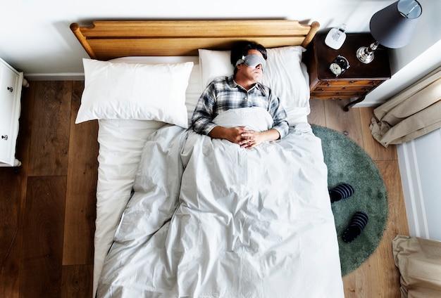 Uomo giapponese che dorme sul letto con la maschera per gli occhi