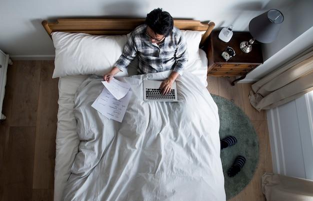 Uomo giapponese che lavora sul letto