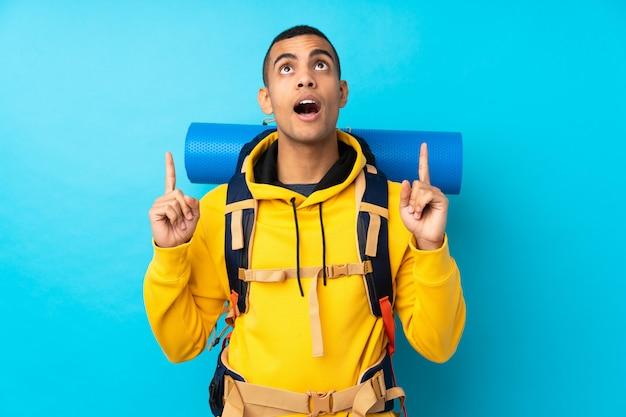 Uomo giovane alpinista con un grande zaino sopra la parete blu isolata che indica con il dito indice una grande idea