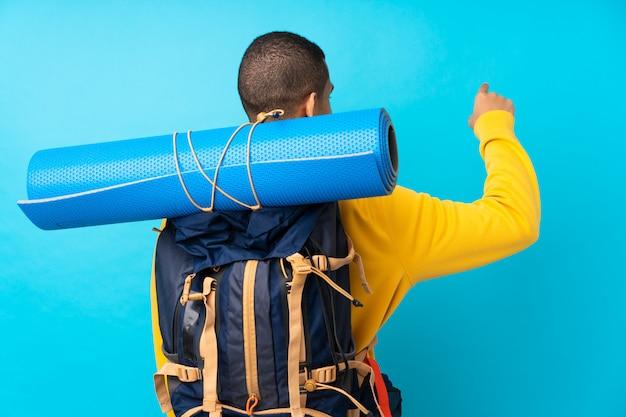 Uomo giovane alpinista con un grande zaino sopra la parete blu isolata che punta indietro con il dito indice
