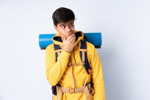 Uomo giovane alpinista con un grande zaino su blu isolato pensando un'idea
