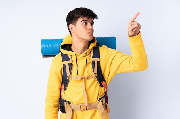 Uomo giovane alpinista con un grande zaino su sfondo blu isolato toccando sullo schermo trasparente