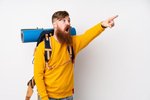 Uomo giovane alpinista con un grande zaino sul muro bianco isolato che punta lontano