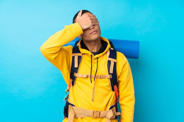 Uomo giovane alpinista con un grande zaino sul muro blu isolato che copre gli occhi a mano