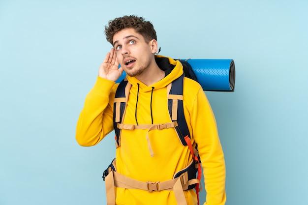 Uomo giovane alpinista con un grande zaino sulla parete blu che ascolta qualcosa