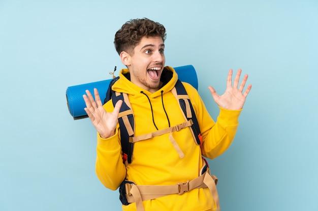 Uomo giovane alpinista con un grande zaino sulla parete blu con espressione facciale a sorpresa
