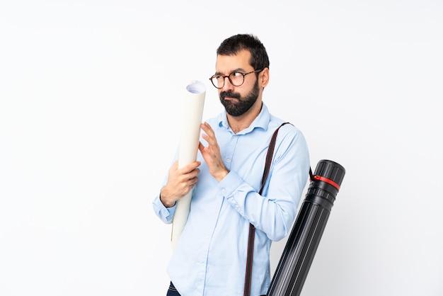 Uomo giovane architetto con la barba che complotta qualcosa