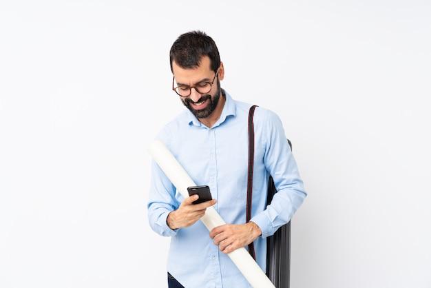 Uomo giovane architetto con la barba che invia un messaggio con il cellulare