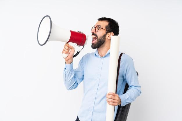 Uomo giovane architetto con la barba su sfondo bianco isolato gridando attraverso un megafono