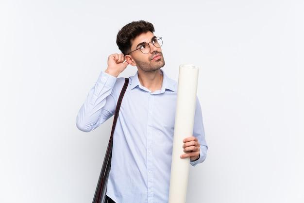 Uomo giovane architetto su sfondo bianco isolato con dubbi e con espressione del viso confuso