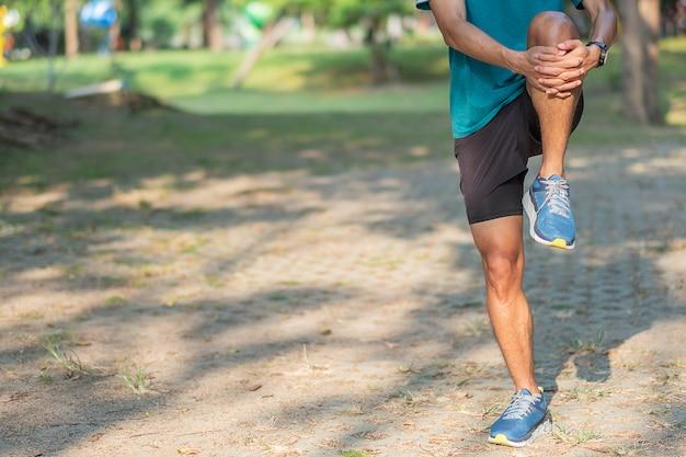 Uomo giovane atleta che si estende nel parco all'aperto.