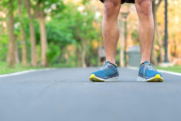 Uomo giovane atleta con scarpe da corsa nel parco all'aperto