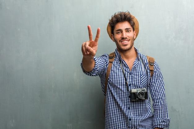 Uomo giovane bello viaggiatore che indossa un cappello di paglia, uno zaino e una macchina fotografica che mostra numero due, simbolo del conteggio, concetto di matematica, fiducioso e allegro