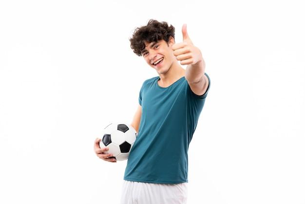 Uomo giovane calciatore sopra il muro bianco isolato con il pollice in alto perché è successo qualcosa di buono