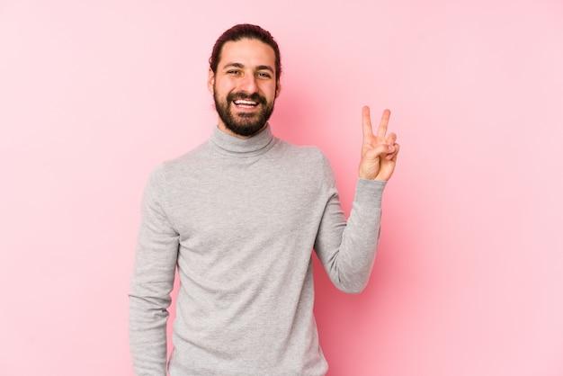Uomo giovane capelli lunghi gioioso e spensierato mostrando un simbolo di pace con le dita