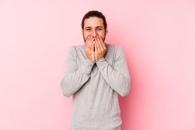 Uomo giovane capelli lunghi isolato su rosa ridere di qualcosa, coprendo la bocca con le mani.