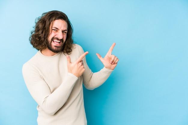 Uomo giovane capelli lunghi isolato su un puntamento blu con gli indici verso uno spazio di copia, esprimendo eccitazione e desiderio.