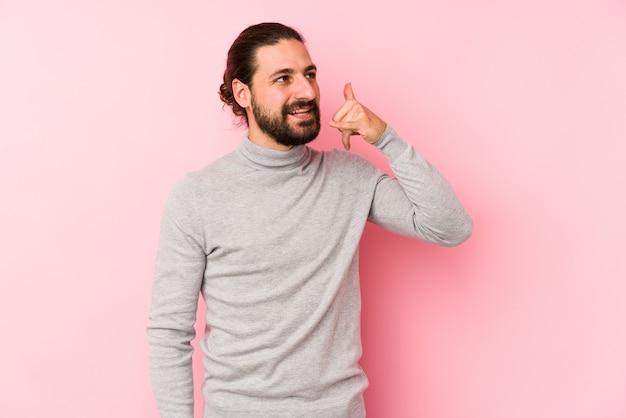 Uomo giovane capelli lunghi isolato su un rosa che mostra un gesto di chiamata di telefono cellulare con le dita.