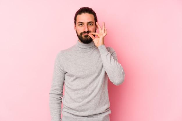 Uomo giovane capelli lunghi isolato sul rosa con le dita sulle labbra mantenendo un segreto.