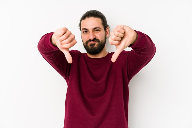 Uomo giovane capelli lunghi su un muro bianco che mostra il pollice verso il basso e che esprime antipatia.