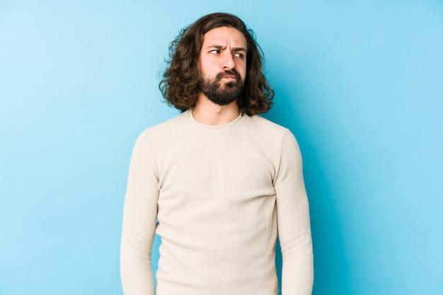 Uomo giovane capelli lunghi su una parete blu confuso, si sente dubbioso e incerto.